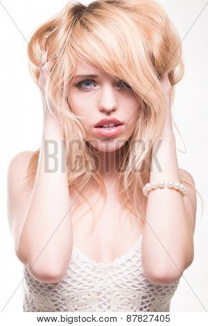 Sexy Young Blond Woman with Hands in Hair Looking Distressed, in Studio with White Background