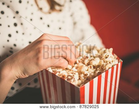 Young Woman Eating Popcorn In Movie Theater