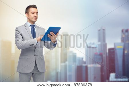 business, people and technology concept - happy businessman in suit holding tablet pc computer over city background