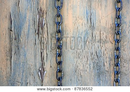 Chain on weathered wooden background concept