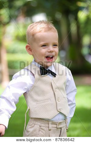 Happy handsome little boy in a suit in park