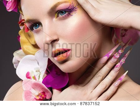 Beautiful woman with long nails, perfect skin, hair of orchids. Beauty face