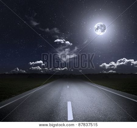 Asphalt road through the green field and moonlight. Elements of this image furnished by NASA