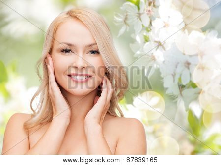 beauty, people, summer, spring and health concept - beautiful young woman touching her face over green blooming garden background