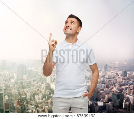 happiness, gesture and people concept - smiling man pointing finger up over city background