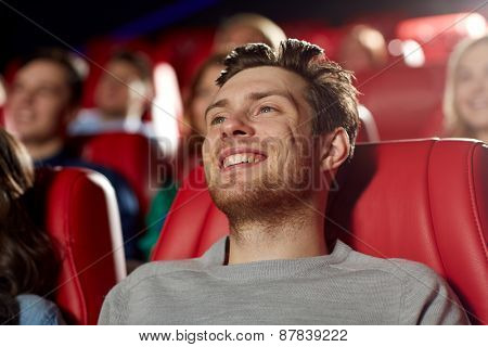 cinema, entertainment and people concept - happy young man watching comedy movie in theater