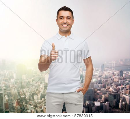 happiness, gesture and people concept - smiling man showing thumbs up over city background