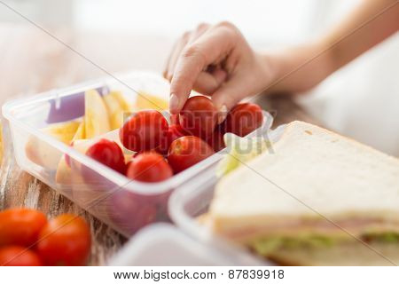 healthy eating, storage, dieting and people concept - close up of woman with food in plastic container at home kitchen