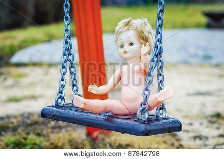 Old abandoned doll on a swing at outdoors