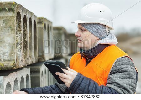Civil engineer with tablet PC near the construction panels