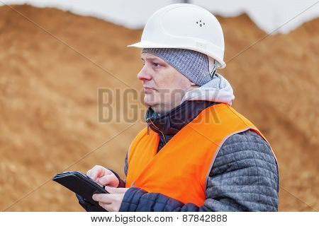 Civil engineer with tablet PC at a pile of sand