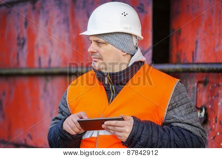 Worker with tablet PC near the red metal door