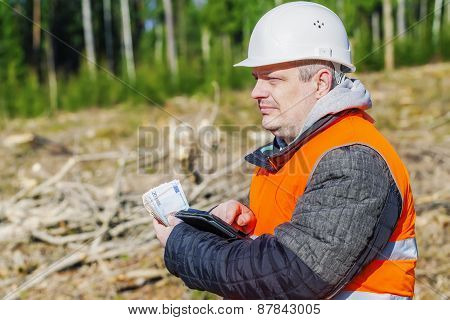 Lumberjack with money in forest