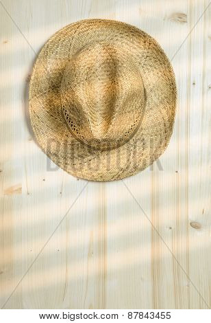 A Straw Hat hanging on a Wall