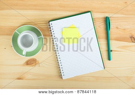 Notebook Pen And Empty Cup In Wood Table