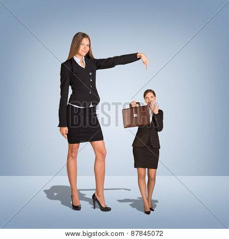 Smiling Young Businesswoman Pointing to small woman with briefcase