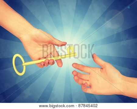 Hand passing a gold key