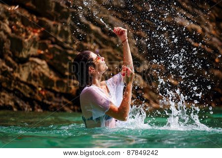 Beautiful girl playing with emerald water