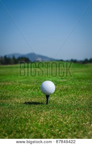 Golf Ball On Teeing Area With Green Grass Ahead And Mountains In Background. Soft Focus Or Shallow D