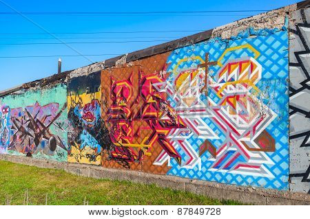 Colorful Graffiti Patterns Over Old Concrete Garage Wall