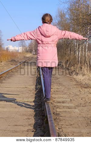 Girl balancing on railway tracks