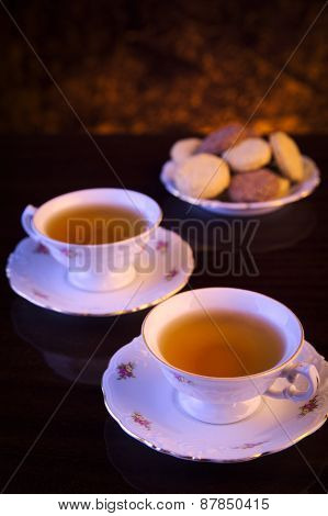 Old-style Kettle With Two Cups Of Tea With Cookies On Black