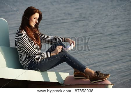 Young girl playing with a paper boat on the shore of a lake