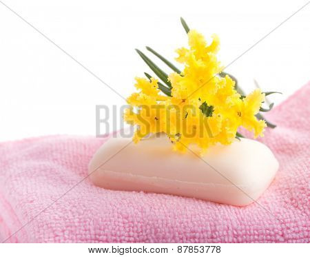 Soap on pink, soft wash cloth with a yellow wildflower on top, on white background