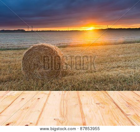 Stubble Field At Sunset With Old Wooden Planks Floor On Foreground