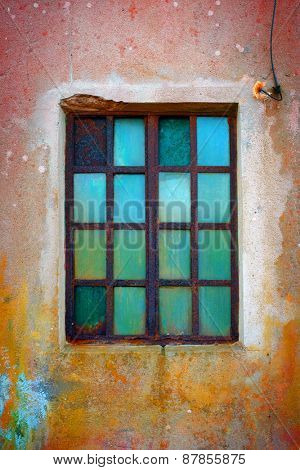 Grungy window with rusty iron bars and green old glass