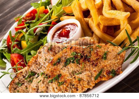 Fried steaks, French fries and vegetables