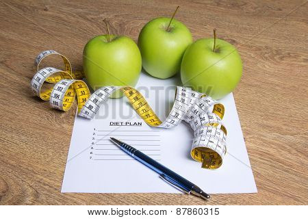 Weightloss Concept - Close Up Of Paper With Diet Plan, Apples And Measure Tape On Table