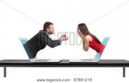 virtual couple got out of the computers. amazed happy woman looking at gift and happy man looking at her. isolated on white background