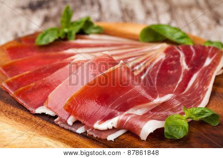sliced prosciutto on a wooden table