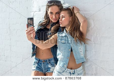 Girls friends taking selfie picture. Two beautiful young women having fun making photo and grimacing