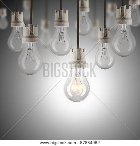 hanging light bulbs with single one shinning