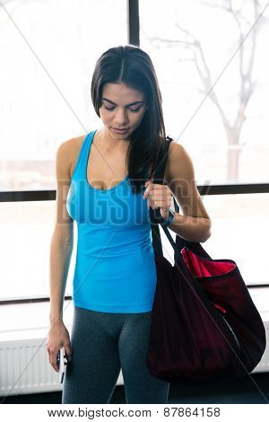 Young fit woman standing with bag and smartphone in gym