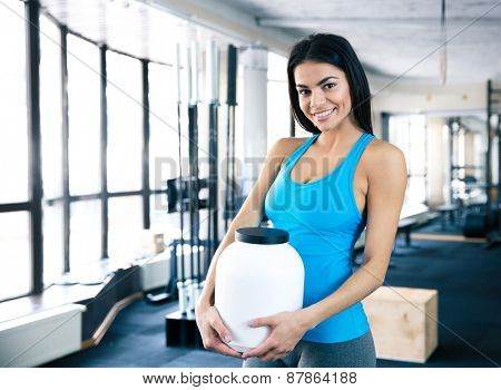 Happy woman holding plastic container with sports nutrition at gym and looking at camera