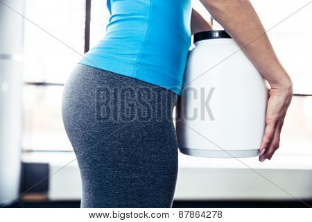 Closeup image of female body with plastic container at gym
