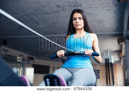 Attractive young woman working out on training simulator at fitness gym