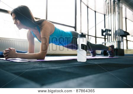 Young fit woman working out on yoga mat at gym
