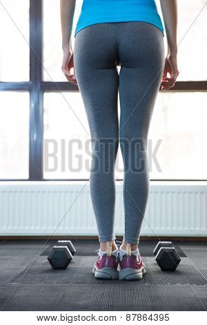 Back view portrait of a woman standing at gym with dumbbells