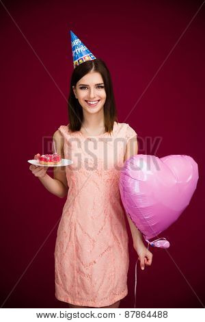 Woman holding heart shaped balloon and donut with candle over pink background. Looking at camera. Wearing in dress. Celebrating birthday