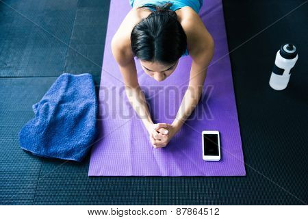 Top view portrait of a young woman doing yoga exercises on yoga mat at gym