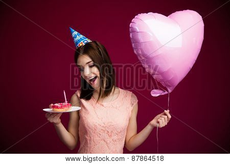 Happy young woman holding donut with candle over pink background
