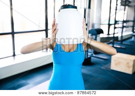 Closeup portrait of a woman covering her face with plastic container at gym