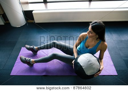 Young woman working out with fit ball on yoga mat at gym