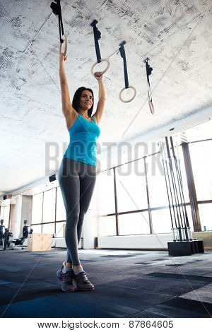 Full length portrait of a beautiful young woman doing exercise on gimnastic rings at gym