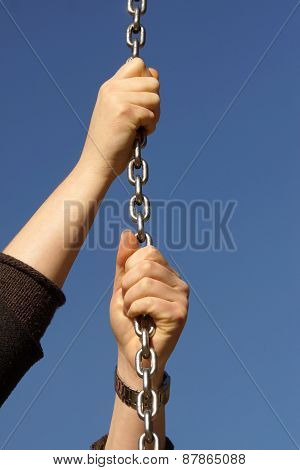 Beautiful woman hand and steel chain
