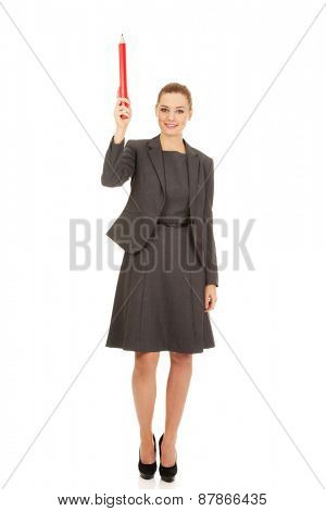 Attractive modern businesswoman pointing up with pencil.